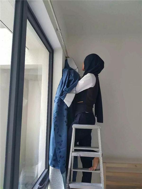 女管家在给业主安置窗帘